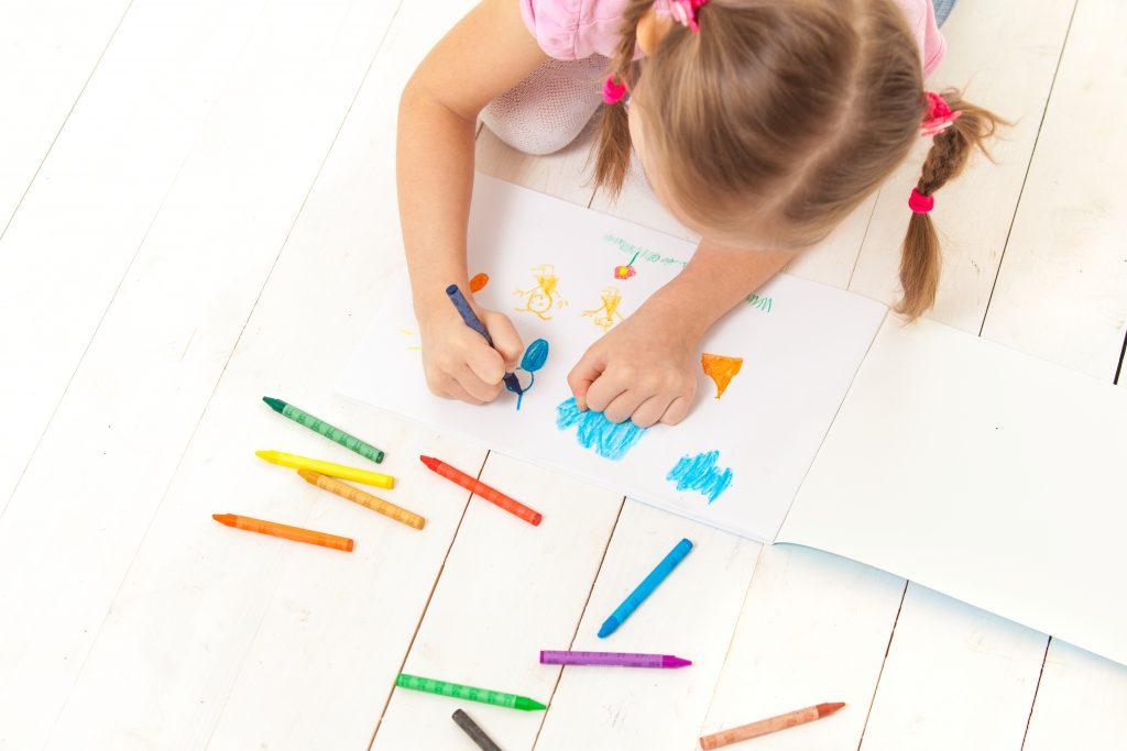 niña coloreando en casa